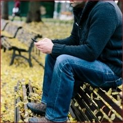 man sitting outside on bench with phone