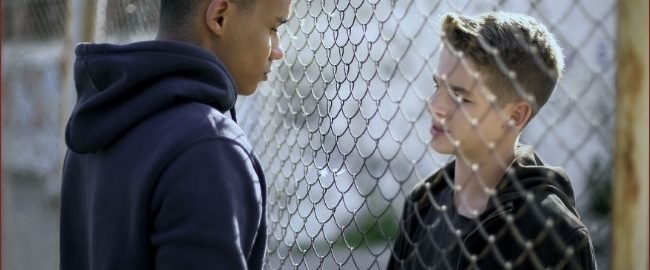 young men talking through fence